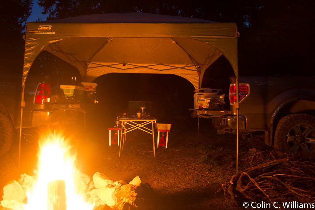 Picture of the campsite, with a campfire, table and two trucks with their tailgates facing each other.
